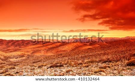 Futuristic landscape, beautiful dramatic red sunset over hot dry wild desert, amazing lands of wilderness - stock photo