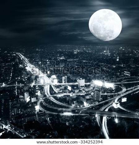 Futuristic night aerial view panorama of Bangkok skyline at full moon night under dramatic cloudy sky. Bangkok, Thailand - stock photo