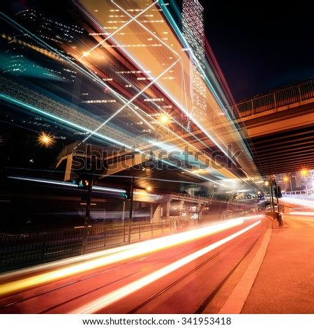 Futuristic night cityscape view with illuminated skyscrapers and city traffic across street. Hong Kong - stock photo