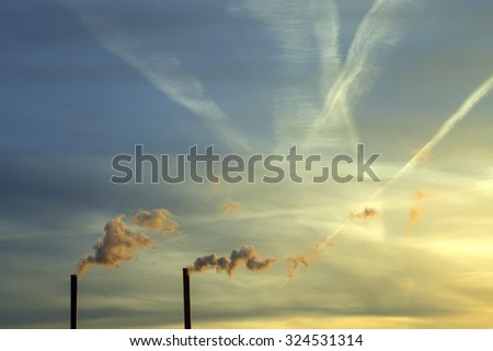 Futuristic sky with chimneys smoke and traces of many planes in the sky. For background.