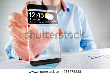 Futuristic Smart phone (phablet) with a transparent display in human hands. Concept actual future innovative ideas and best technologies humanity.