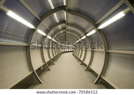 Futuristic tunnel with circular construction and glass windows - stock photo