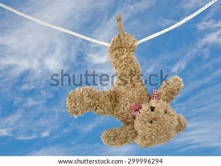 fuzzy brown teddy bear hanging on a clothesline with retro wooden clothespins - stock photo