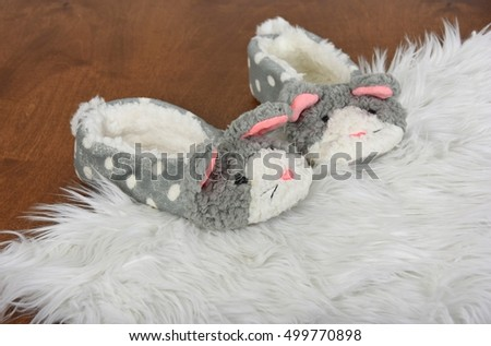 fuzzy bunny slippers on white fur rug and wood floor