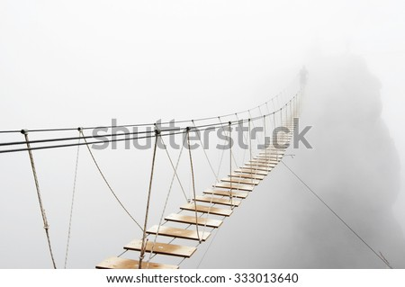 Fuzzy man walking on hanging bridge vanishing in fog. Focus on middle of bridge.