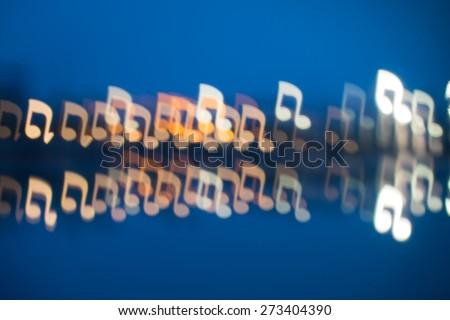 Fuzzy music notation shaped lights, defocused background - stock photo