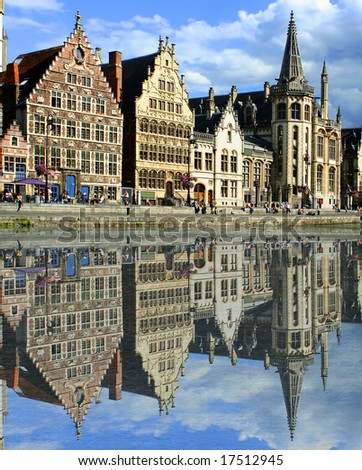 gabled houses along a canal  in Gent,  Belgium with reflection on the water - stock photo