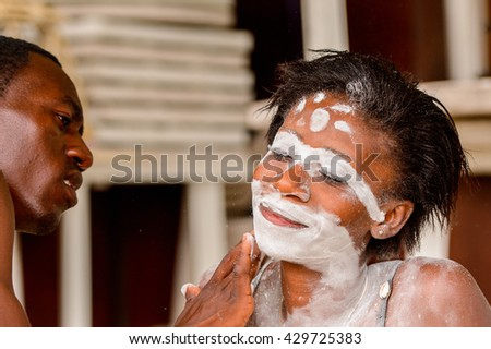 GABON - MARCH 6, 2013: Unidentified Gabonese man put the white paint on his girlfriend's face in Gabon, Mar 6, 2013. White paint symbolizes connection with ancestores.