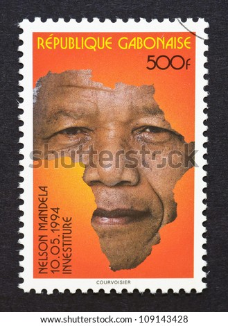 Gabonese Republic - CIRCA 1994: postage stamp printed in Gabonese Republic showing an image of Nelson Mandela with the african continent, circa 1994. - stock photo