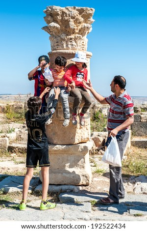GADARA, JORDAN - MAY 2, 2014: Unidentified tourists near the column in Gadara, Jordan. By the third century BC the Gadara town was of some cultural importance.
