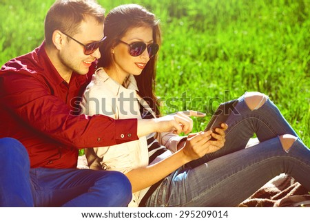 Gadget users concept. Two smiling lovers in trendy clothing and eyeglasses using tablet in autumn park. White shiny smiles. Urban style. Close up. Copy-space. Outdoor shot