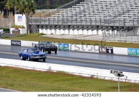 GAINESVILLE, FL - DECEMBER 6: A 1972 Oldsmobile 442 driven by Bart Treadwell and a Pontiac Firebird seen racing at the Florida Finals at the NHRA Gainesville Raceway on 12/6/2009.