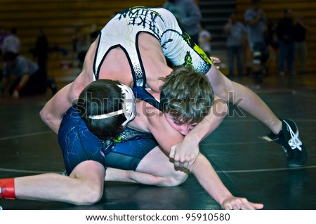 GAINESVILLE, GA, USA - FEB 11: Andy Leggett, winner, held by an unidentified opponent in the 11-14 division of a wrestling tournament, February, 11, 2012, North Hall High School Gainesville, GA. - stock photo