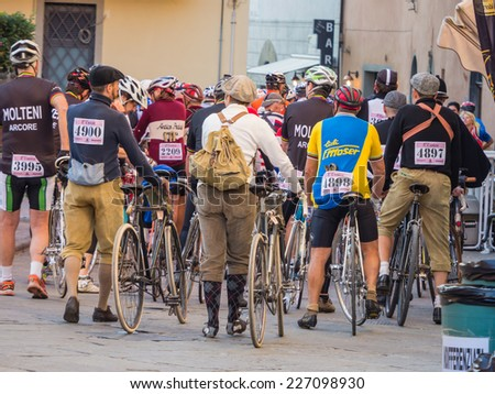 GAIOLE IN CHIANTI, ITALY - 5 OCT. 2014: Unidentified participants of L'Eroica, a historic cycling event for owners of vintage bicycles and apparel who ride through Tuscany on white gravel roads - stock photo