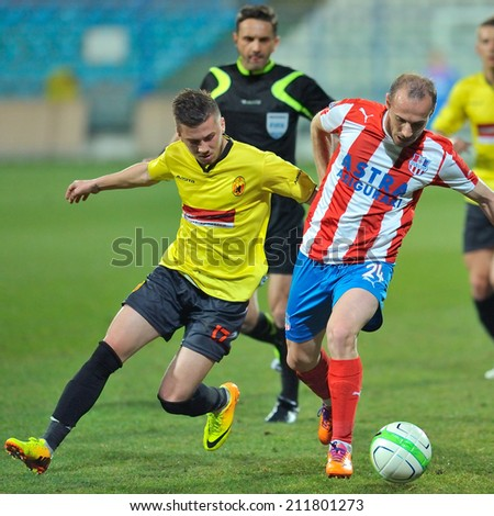 GALATI, ROMANIA - APRIL 6: Unknown football players performs during the soccer game in Liga 1, score 1-1, Otelul Galati (red and white) vs Ceahlaul Piatra Neamt (yelow), April 6, 2014, Galati, Romania