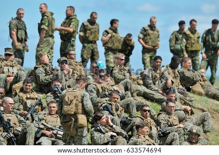 GALATI, ROMANIA - MAY 15, 2015: American and Serbian soldiers rest after a shooting session in the polygon, in Galati, Romania, may15, 2015