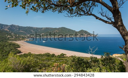 Galeria beach on the west coast of Corsica with boats moored in the blue Mediterranean sea - stock photo