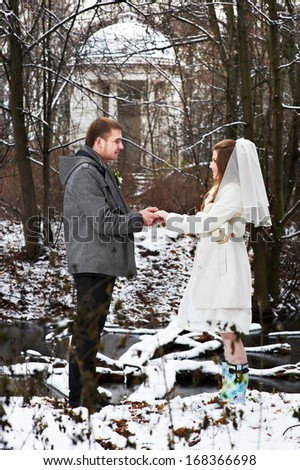 Gallant groom and bride in winter woods on wedding day