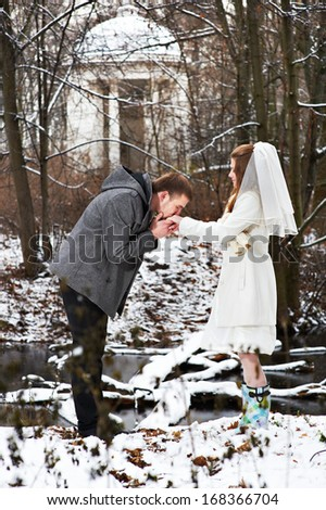 Gallant groom kissing bride's hand in the winter woods on wedding day