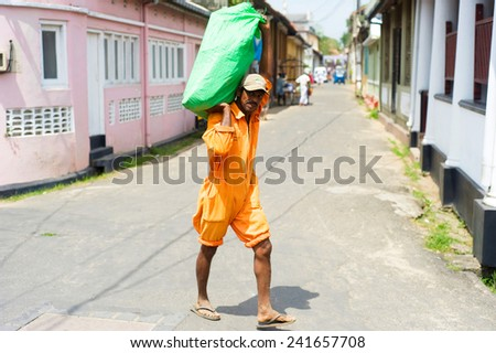 GALLE, SRI LANKA - 26 JAN, 2012: Worker with a big packet walking on the street - stock photo