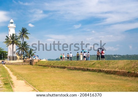 GALLE, SRI LANKA - MARCH 9, 2014: Tourists in front of the oldest Sri Lankan lighthouse placed inside the walls of the ancient Galle fort, a UNESCO world heritage site. - stock photo