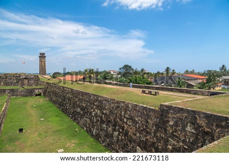 GALLE, SRI LANKA - MARCH 9, 2014: Walls of Galle fort with clock tower in distance.  Fort was originally built in 1684 to house the Dutch Governor and his staff and today is UNESCO World Heritage Site - stock photo