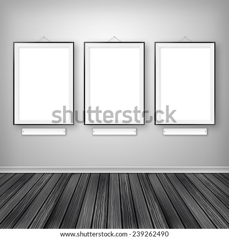 Gallery interior with three empty frames on wall.
