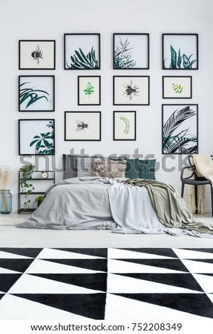 Gallery of floral posters above king size bed in spacious bedroom with black and white