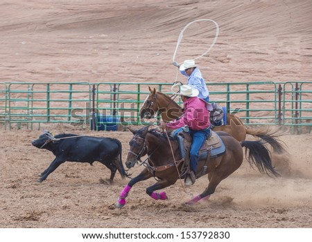 GALLUP , NEW MEXICO - AUGUST 10 : Cowboys Participates in in a Calf roping Competition at the 92nd annual Indian Rodeo in Gallup, NM on August 10 2013 - stock photo