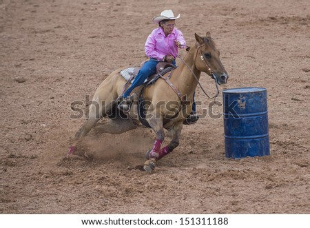 GALLUP , NEW MEXICO - AUGUST 10 : Cowgirl Participant in a Barrel racing competition at the 92nd annual Indian Rodeo in Gallup, NM on August 10 2013 - stock photo
