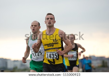 GALWAY, IRELAND - AUGUST 11: Peadar  Harvey and other athletes compete during annual Corrib Oil Streets of Galway 8K road race, on August 11, 2012 in Galway, Ireland.