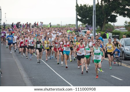 GALWAY, IRELAND - AUGUST 11: Unidentified athletes compete during annual Corrib Oil Streets of Galway 8K road race, on August 11, 2012 in Galway, Ireland.