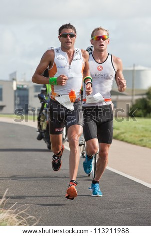 GALWAY, IRELAND - SEPTEMBER 2: T. Bozzone and  Jan Van Berkel, Winner, competing at the Course-Run during 2nd Edition of the Ironman 70.3 Galway 2012 Triathlon,on September 2, 2012 in Galway, Ireland. - stock photo
