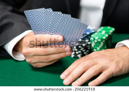 Gambler playing poker cards with chips on the table. Addiction to the gambling - stock photo