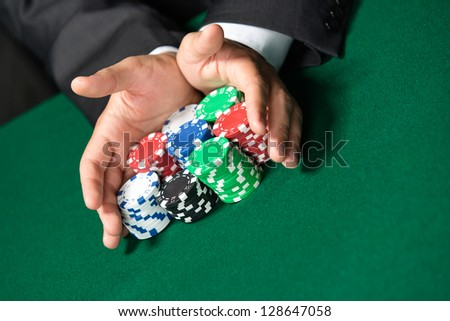 "Gambler stakes ""all in"" pushing his poker chips forward. Risky entertainment of gambling - stock photo"