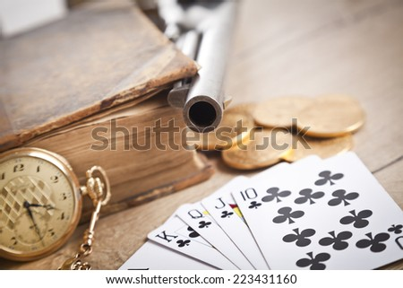 gambling and crime concept with gun, cards and golden coins - stock photo