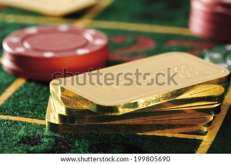 Gambling chips and gold bars on roulette table - stock photo