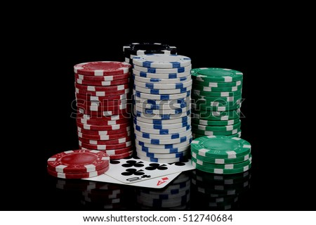 gambling chips and playing cards on black background