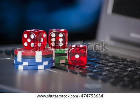 Gambling chips and red dice on laptop keyboard background, online gaming