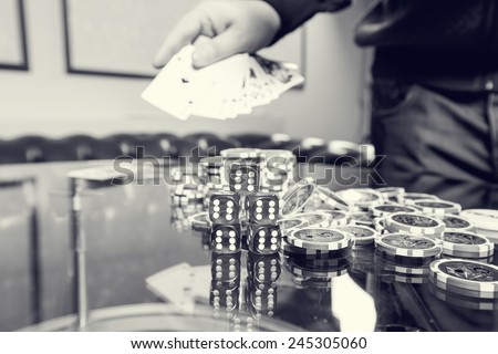Gambling, male players. On the gaming tables are red dice, cards, casino chips - concept gambling addiction. People tend to take risks and to gambling. Play and win the success of the player. - stock photo