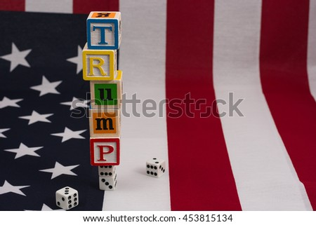 Gambling on Trump.  Trump spelled out with letter blocks, stacked on top of a pair of dice, with an American flag background.