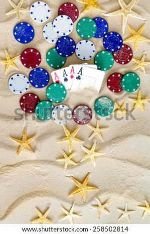 Gambling on Vacation Concept - White Sand with Yellow Stars, Colored Poker Chips and Four Ace Cards. - stock photo