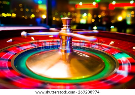Gambling with colorful spinning fortune roulette wheel in casino with swallow depth of field on bokeh casino and city lights in the background - stock photo