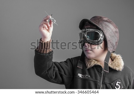game, child playing the aircraft pilot with hat and retro bomber jacket - stock photo