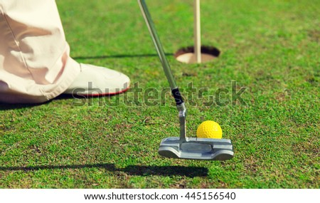 game, entertainment, sport, people and leisure concept - close up of man playing golf and putting ball with metal club into hole on golf field