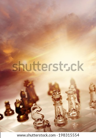 Game of chess pieces in front of bright sky - stock photo