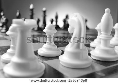 Game of chess with chess pieces lined up on their squares on either side of the board ready for a challenge with selective focus to one white pawn - stock photo
