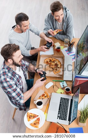 Game time. Top view of three young men playing computer games and eating pizza while sitting at the desk  - stock photo
