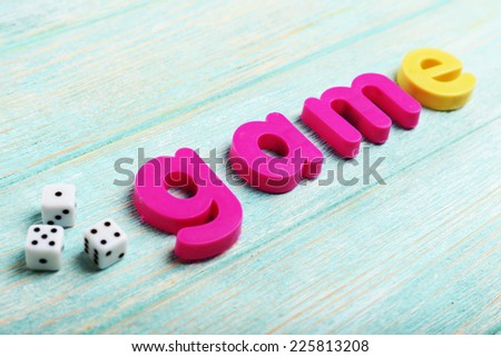 Game word formed with colorful letters on wooden background - stock photo