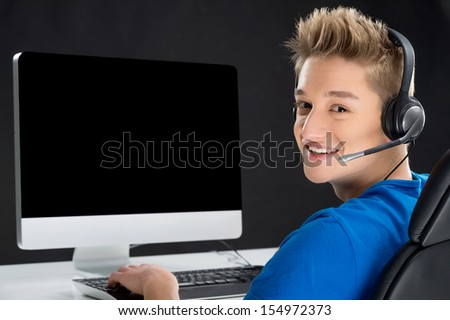 Gamer. Rear view of teenage boy playing video games at his computer and looking over shoulder